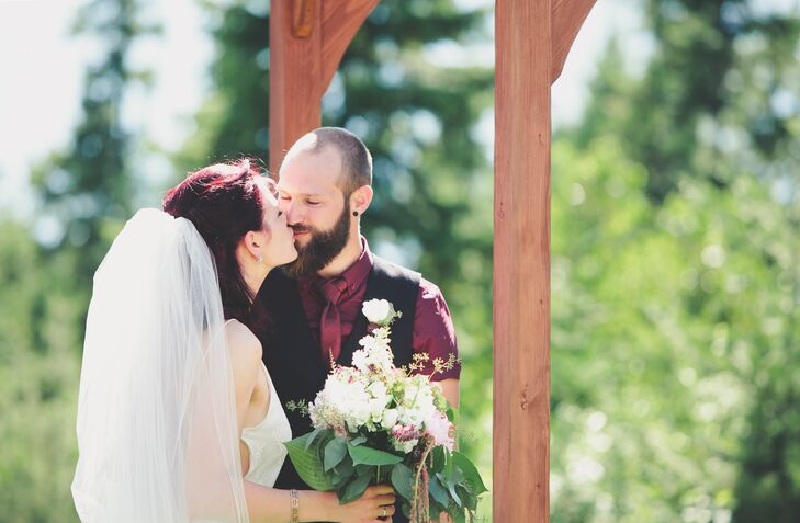 On his wedding day, Sylvan wore a burgundy shirt with a burgundy bow tie and a black vest. Justine and Sylvan were married under a wooden pergola that Sylvan made himself.