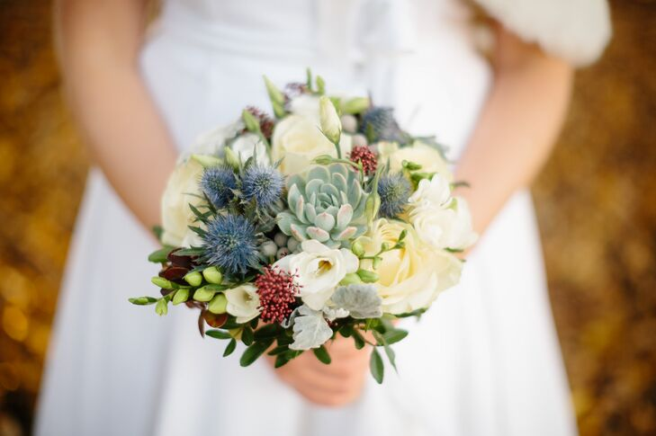 Louise carried a unique bridal bouquet made up of succulents, thistles and holly along with ivory roses and dusty miller for her fall wedding.
