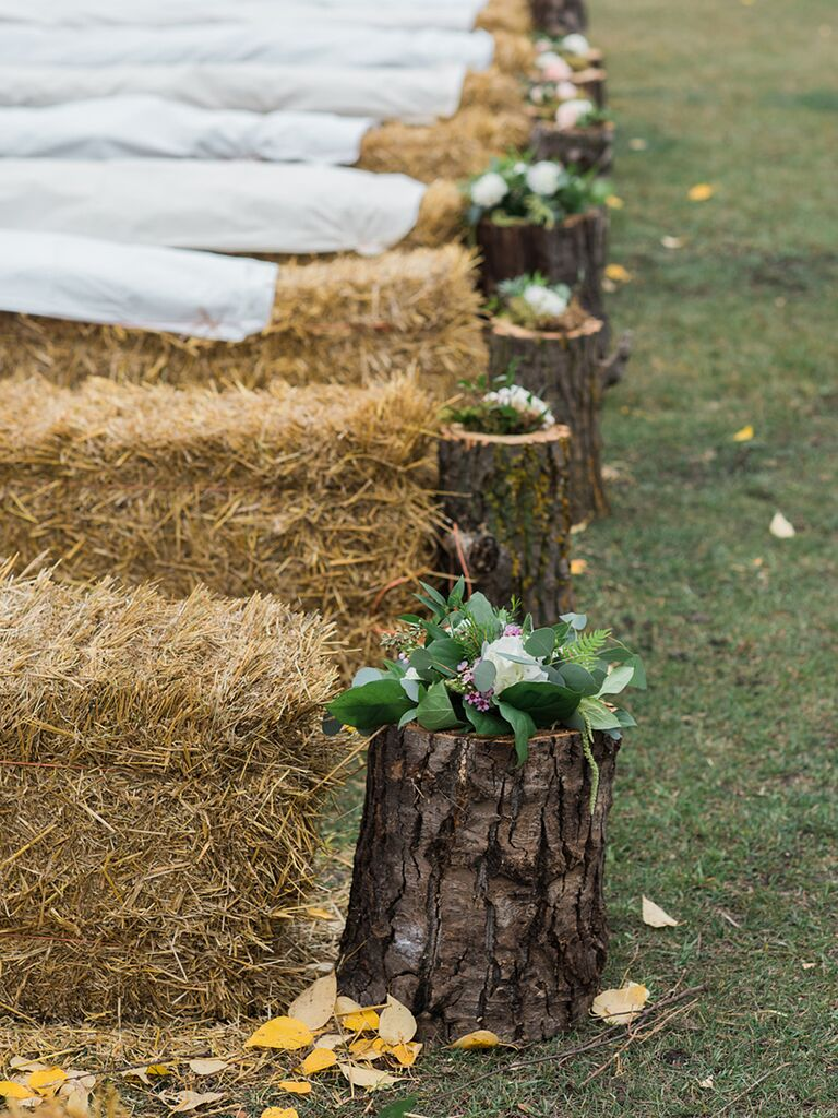 Rustic wedding ceremony aisle decor with timber logs