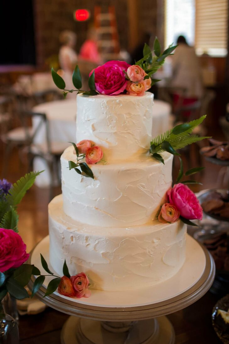 The three-tier pink champagne cake with raspberry filling was covered in white buttercream frosting. The classic dessert filled with flavor had pink and orange flowers accenting the top and sides.