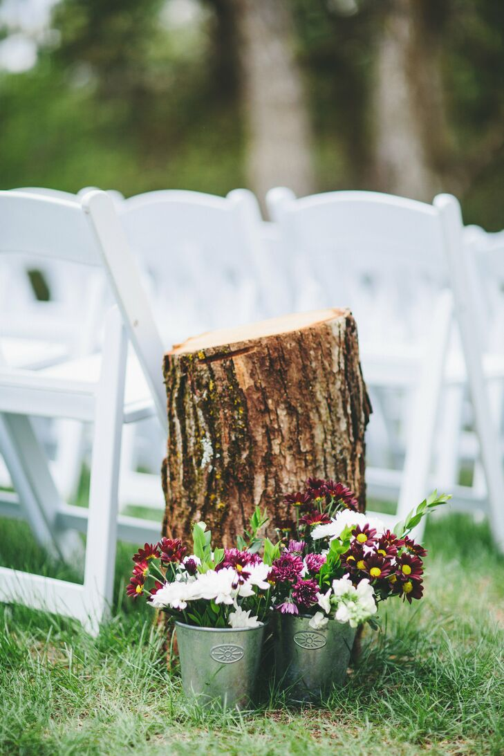 Small galvanized pails filled with stock and mums were placed next to tree stumps along the ceremony aisle.