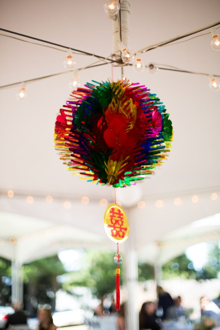A colorful lantern hung from the ceiling of the white tented reception, reflecting Denise's family background among many other wedding day details.