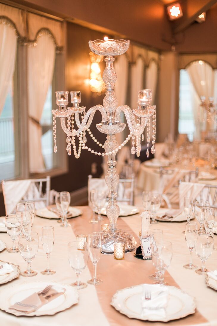 "After Jaris fell in love with the chandeliers at Crystal Ballroom on the Lake  in Altamonte Springs, Florida, she and Angel chose similar crystal candelabras for their centerpieces. Each elegant accent channeled ""The Great Gatsby"" with glamorous draped pearls and even more strands of crystals."