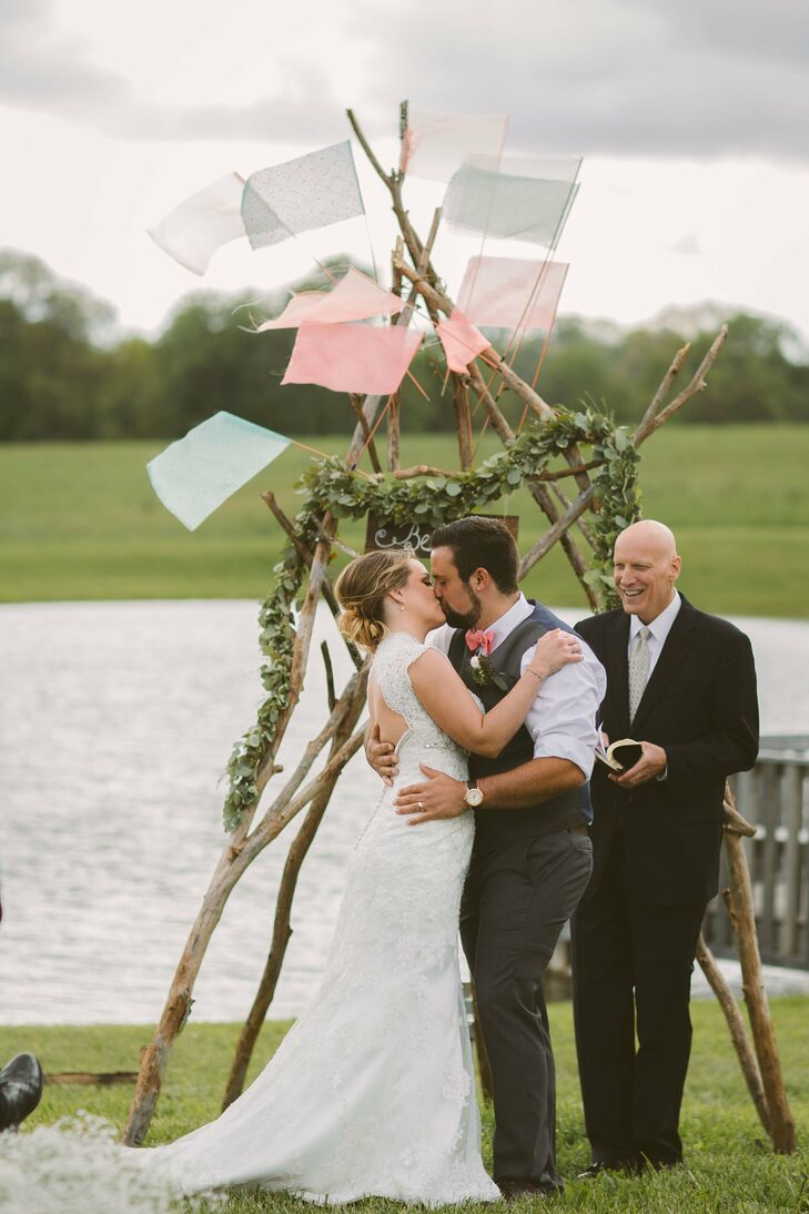 The couple was married in front of a gorgeous lake. Chad built a teepee arbor, and decorated it with coral and blue flags.