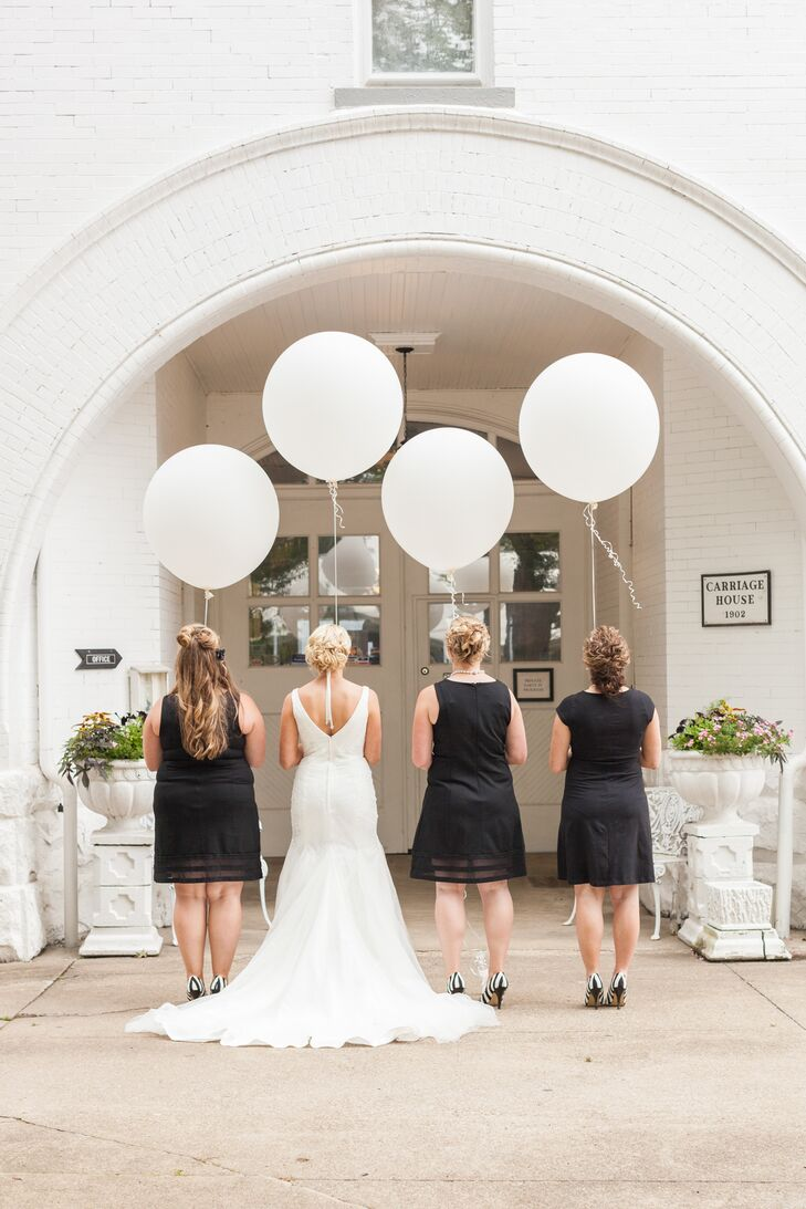 The bride and her bridesmaids stood holding the strings of large white balloons. The bridesmaids wore knee-length black cocktail dresses with black-and-white-striped shoes, which matched the wedding day's classic color palette.