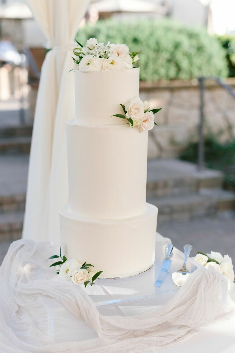 Romantic three-tier white wedding cake with fresh flowers