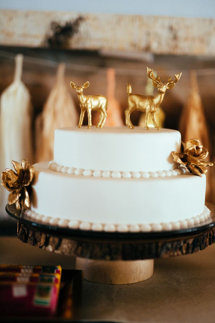 Suzi's mother decorated the simple two-tier white wedding cake with gold spray-painted artificial flowers. She completed the look with a gold buck and doe on top.