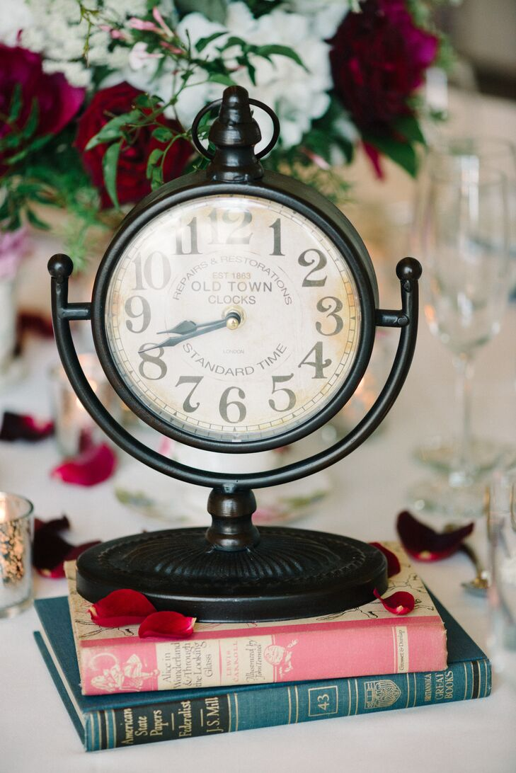 """The White Rabbit would be happy with this centerpiece. Sarah and Steve marked their reception tables with a series of vintage accents, including a pocket-watch-inspired black clock and their own copy of """"Alice in Wonderland."""" Its ivory and pink binding even matched their color scheme."""