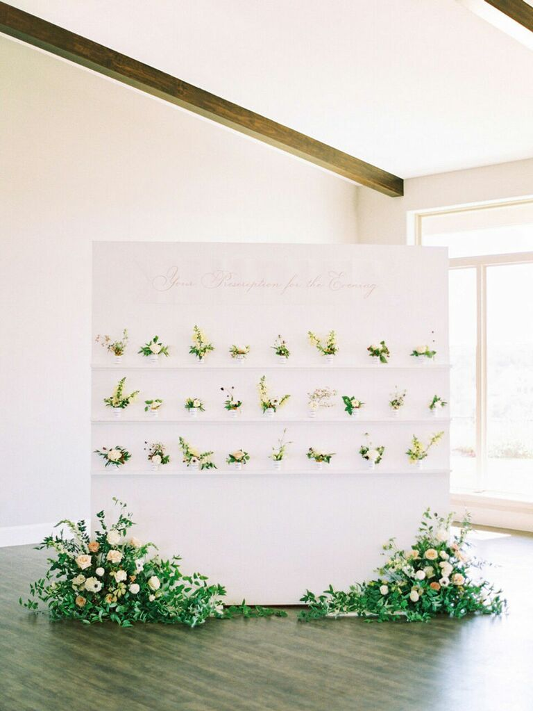 Modern escort card display with small flower pots and large arrangements underneat