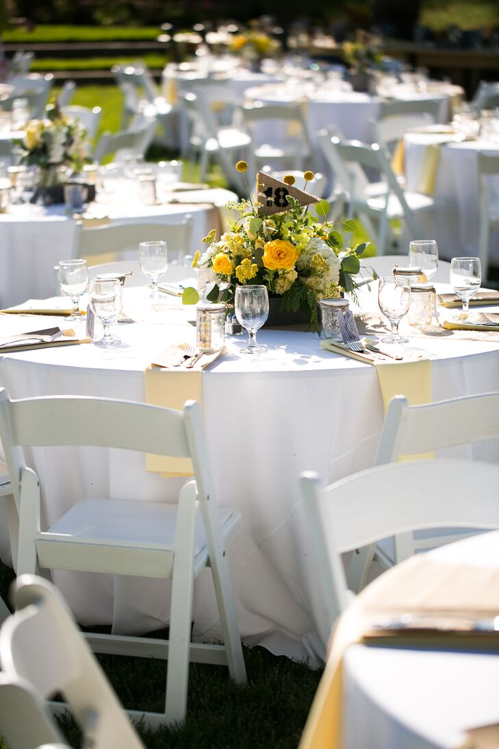 The reception took place outside at Amador Cellars in Plymouth, California, where yellow and green flower arrangements decorated round white dining tables. Burlap flags with numbers at each dining table helped guests find their seats.