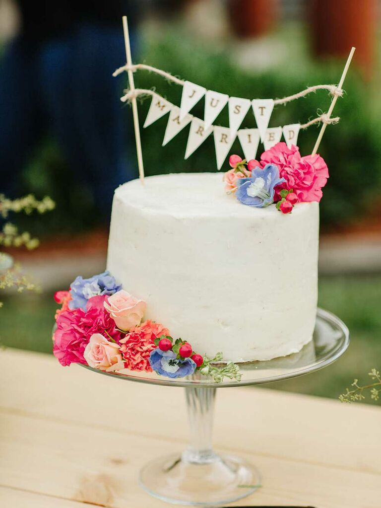 Small wedding cake with colorful flowers and burlap flag topper