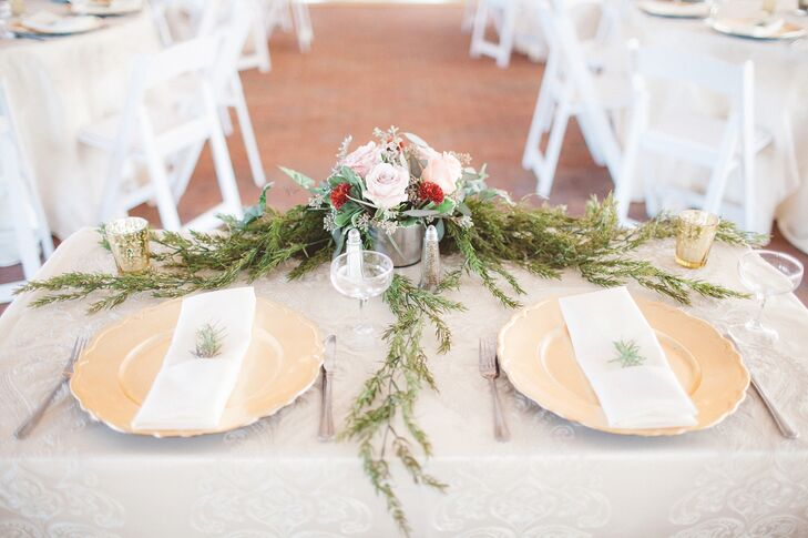 Nikole and Rocco had their sweetheart table decorated with greenery,  votive candles in gold holders and ivory linen. Each place setting, like their guests', had a hint of greenery upon the napkin. A low silver vase arrangement of blush roses and red dahlias was positioned at the front.