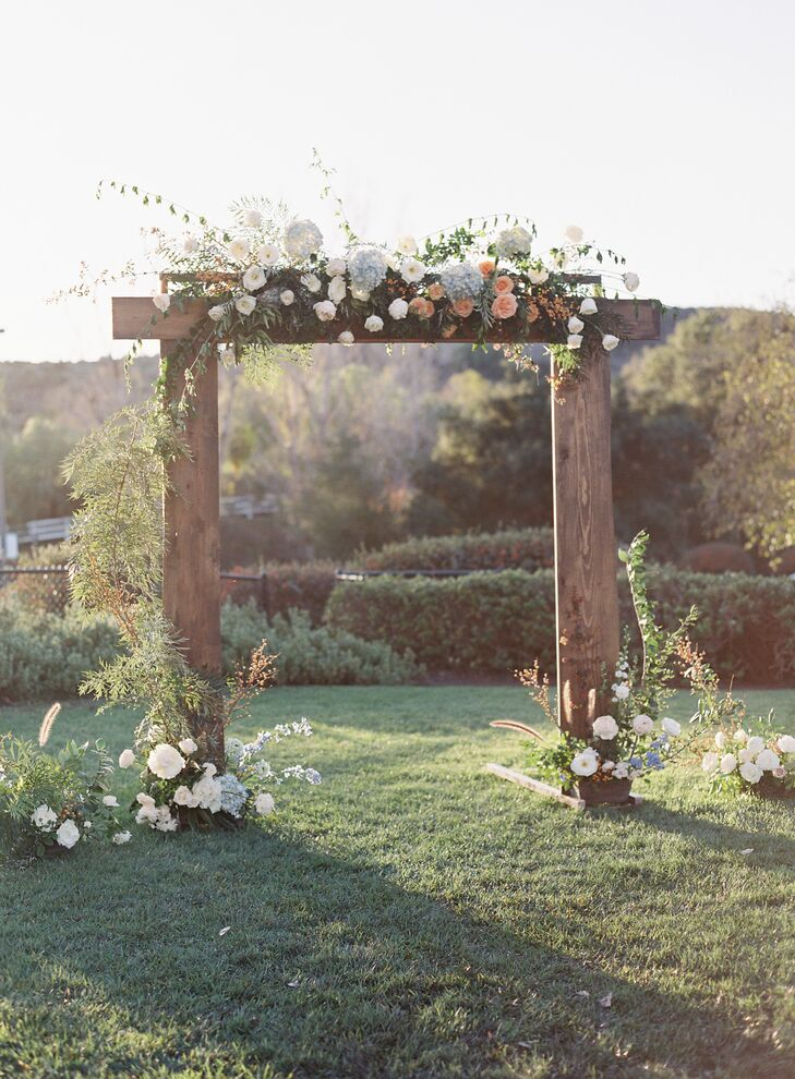 """My favorite detail of the entire wedding would definitely be our grand arch, which was decorated in beautiful flowers,"" Brittany says. ""Our family members even brought it outside to the reception so that we could take more pictures in front of it."""