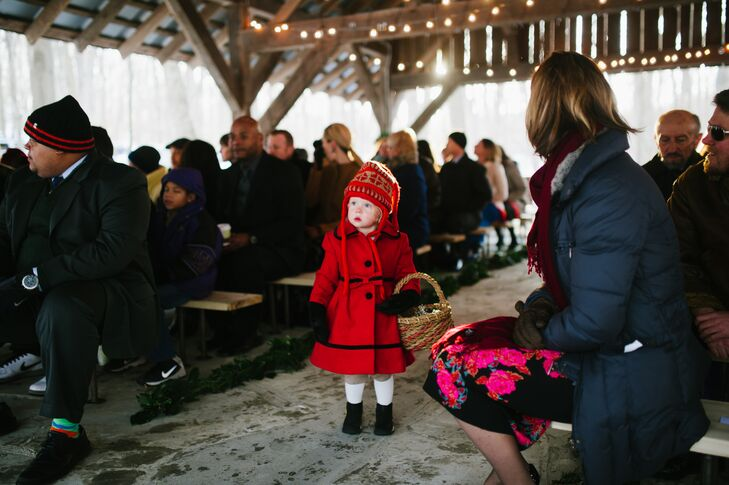 Bundled up in a bright red peacoat and a wool hat, the flower girl and Paula's niece walked down the aisle while holding her woven basket.