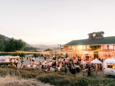Outdoor barn wedding reception with string lights