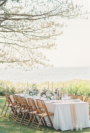 Waterfront Dining Table with Ivory Tablecloth, Wood Folding Chairs and Candles