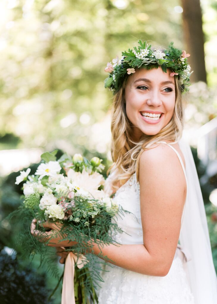 "For the ceremony, Isabella adorned her golden locks with a classic ballet-length veil and a lush ""forest crown."" The florists at Hedgerow Florist created the whimsical pieces with a textured mix of greenery, waxflowers and berries that matched her fern-trimmed bouquet."