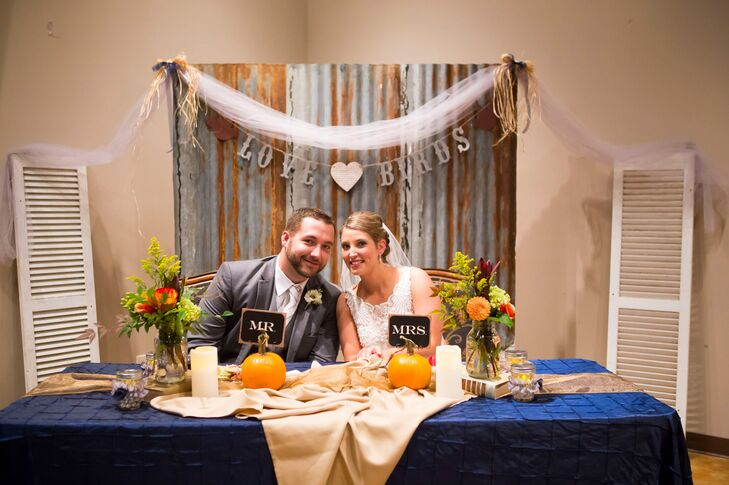 """Nathan built a lot of the things we used, because he is such a handy man,"" Candice says. Their backdrop was a cool shabby-chic rusted board and matching silver banner. For another personal accent, they tied in her love of books by setting a few along the table."