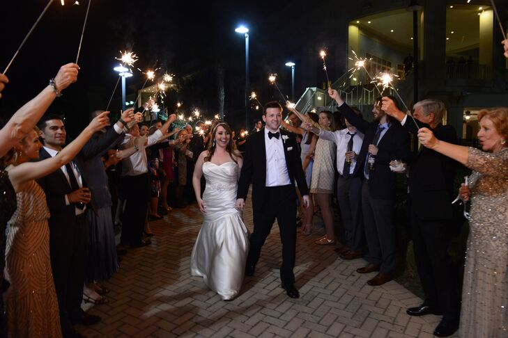 """When the reception was over, the guests headed outside, where they received sparklers,"" Sarah says. ""Jarrett and I walked down steps to a landing, where we proceeded to walk through the arbor of sparklers."""