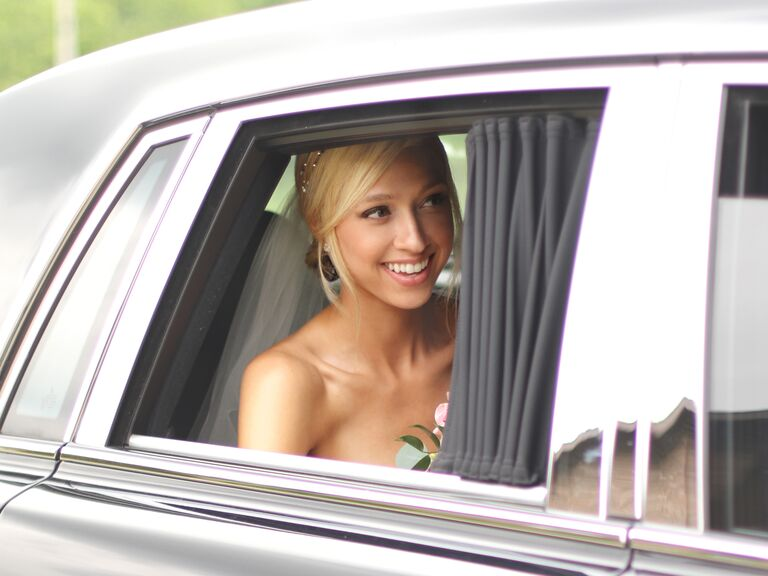 Bride riding in the back seat of a limo to her wedding ceremony