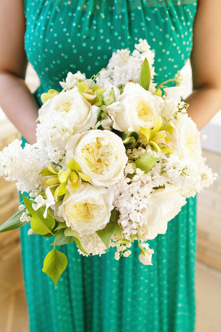 The bridesmaids carried lush bouquets of ivory garden roses, lilacs and lily of the valley with green orchids mixed in for a fresh pop of color.
