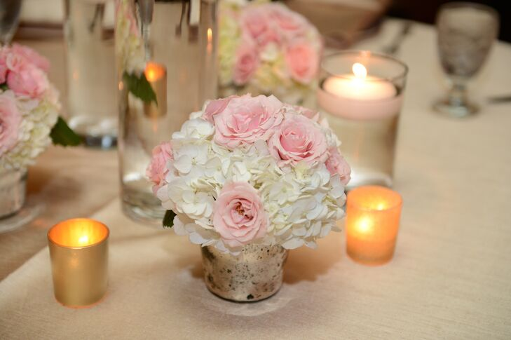 Small arrangements of white hydrangeas and pink roses were paired with small votives for a soft, romantic centerpiece look.