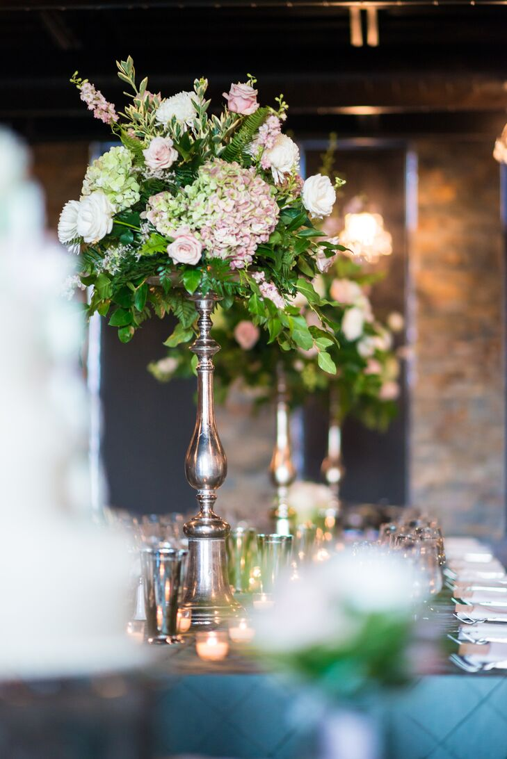 The reception tables were lined with bronze candelabras that were topped by arrangements of blush hydrangeas, ivory roses and greens.
