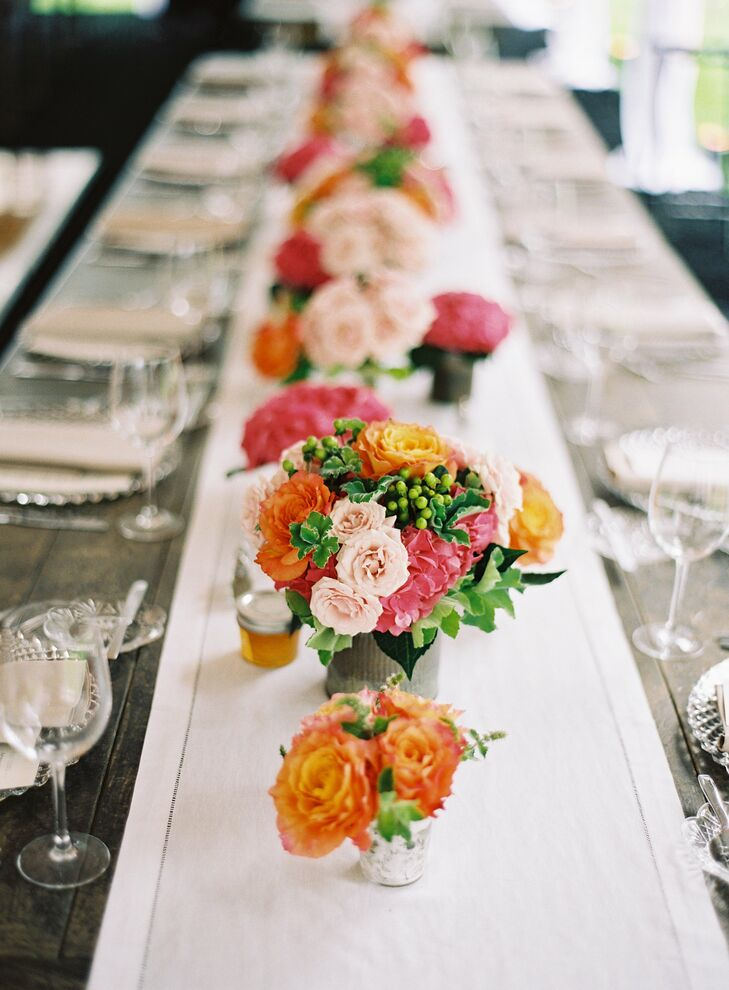 Small bunches of bright tangerine, coral and pink flowers in mercury glass vases were placed down the center of the reception tables.