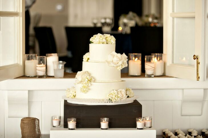 bc02e8d6a8 The couple's three-tiered traditional wedding cake was topped with fresh  white flowers.