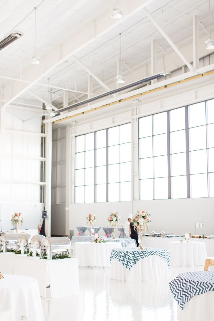 The reception tables were all arranged by airport boarding zones, and Kelsey's dad, a pilot, gave a welcome toast that readied the guests for flight. The dining tables had gold or blue and white chevron overlays that added texture to the monochromatic hangar. The cocktail tables had full-length tablecloths tied in the middle with a coral ribbon.