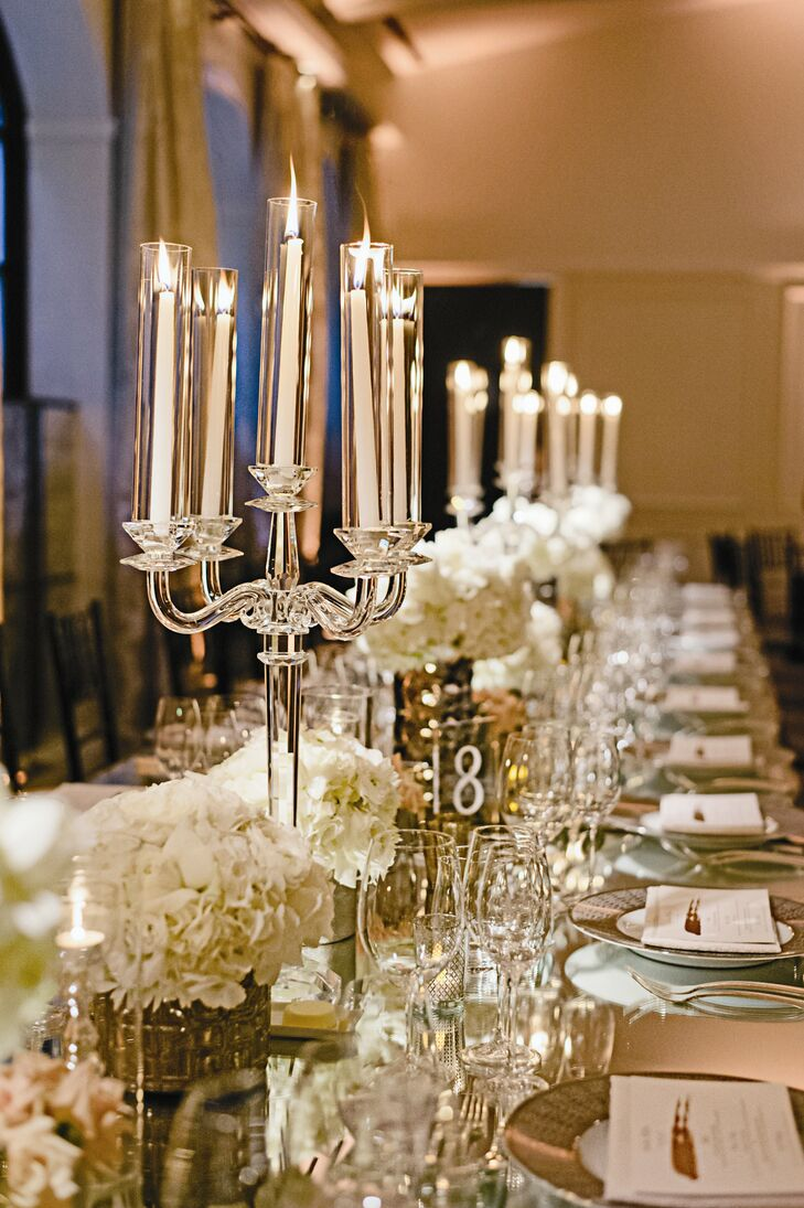 Metallic vases full of cream flowers adorned the mirrored tables, with crystal candelabras rising from them.