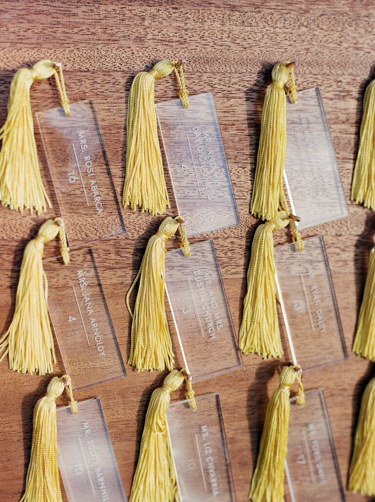 acrylic wedding escort cards hanging on wooden display board with yellow tassels 2021 wedding colors