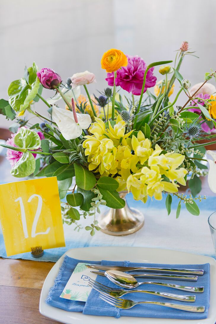 """The day's tropical-inspired palette was reflected in bright yellow place cards, blue hand-dyed linens, dip-dyed tablecloths and napkins. """"It all went along with the watercolor-based design used throughout our stationery and other paper goods,"""" Diana says."""