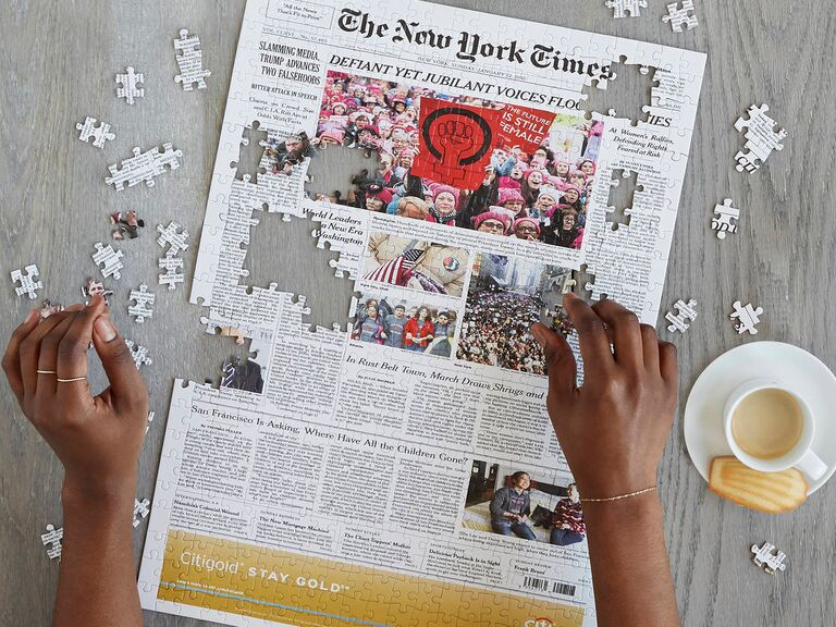 Woman doing puzzle of The New York Times front page