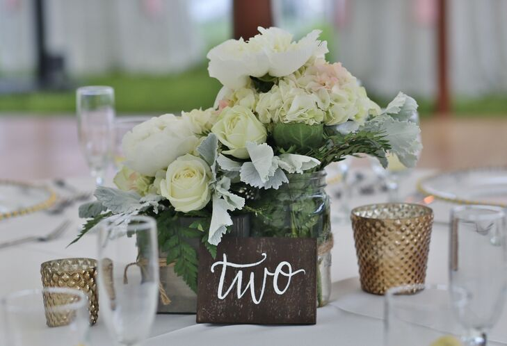 Broad Brook Gardens designed lush low centerpieces for each white linen-covered round table. Both silver breakaway vases and clear mason jars were filled with white roses, white peonies, dusty millers and white hydrangeas. Adding to the couple's shabby chic decor, each table was met with a wooden table number.