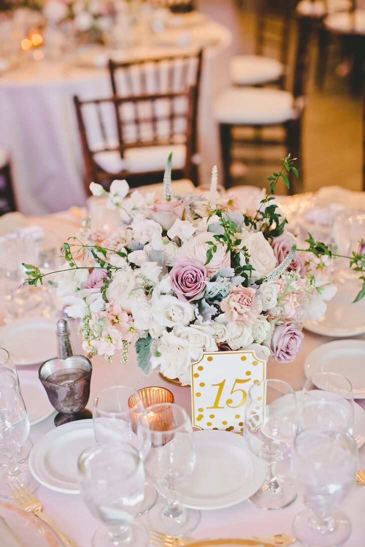 Dining tables covered in white linens had white table numbers decorated with gold polka dots, guiding guests to their seats! Lush arrangements of pastel-colored blooms accented the middle of the table for all to admire.
