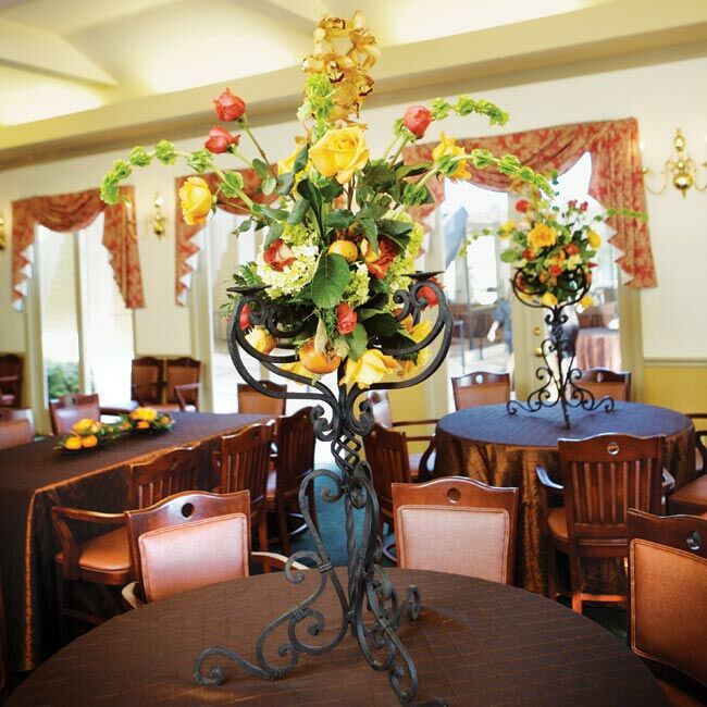 Inside the country club, wrought iron bowls and candelabra held flowers in the wedding colors and persimmons, tying together all of the decor.