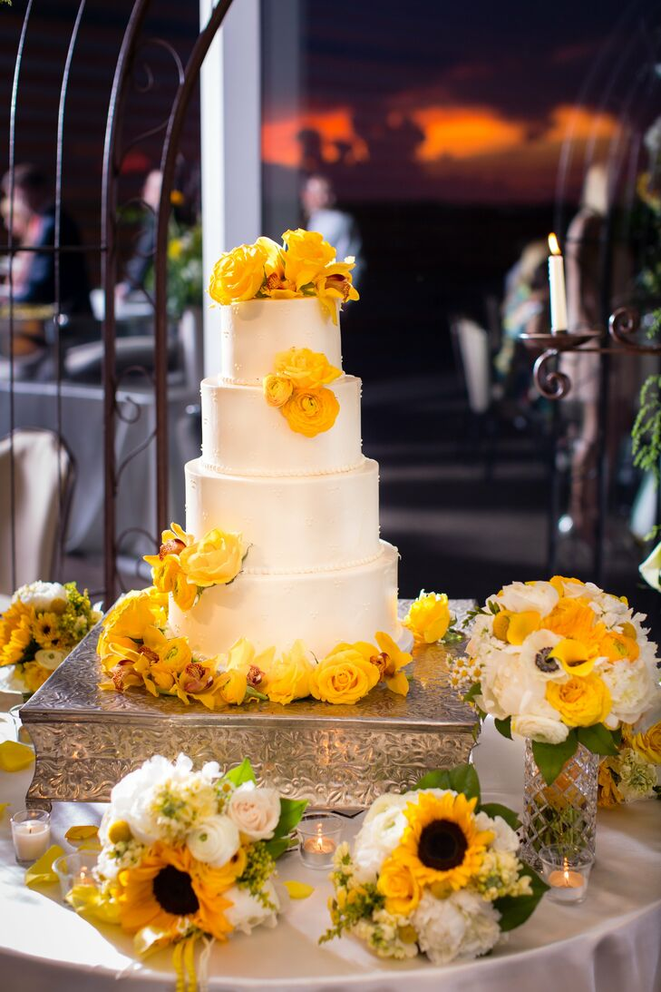 The sweet and simple cake was decorated with Swiss dots and topped with yellow roses and sunflowers.