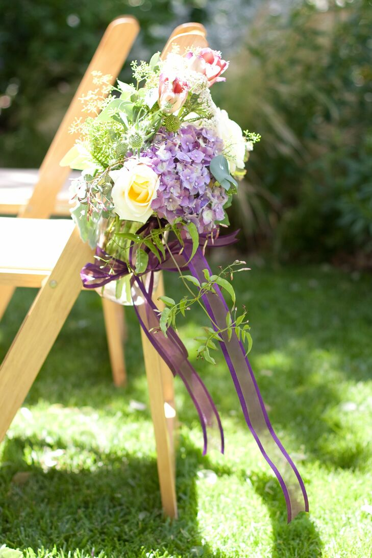 Purple hydrangeas, punk tulips, yellow roses and an abundance of greens set in ribbon-wrapped mason jars decorated the aisles during the ceremony.