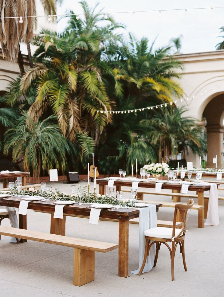 Wooden picnic-style dining tables filled up the outdoor space at Balboa Park in San Diego, California. Settings made up of gold dinnerware covered the tabletops, along with draped garlands and lush, overflowing flower centerpieces.