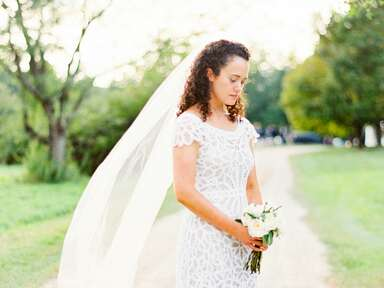 Bride in a macramé grown holding her bouquet.