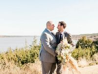 LGBTQ+ couple embracing on rustic lakeside overlook