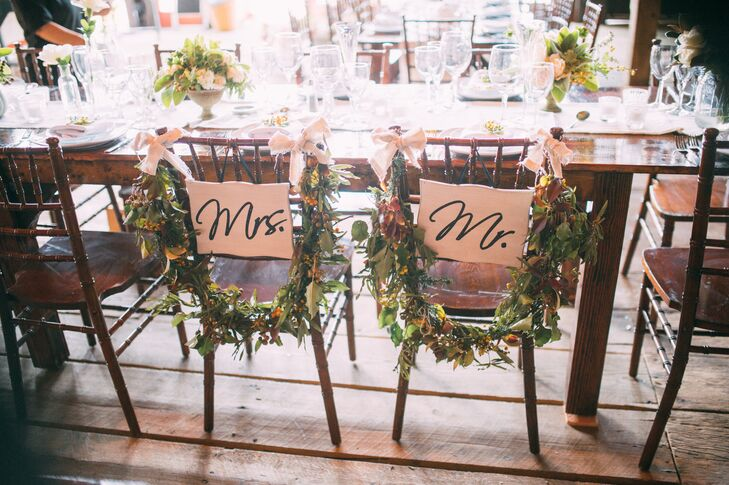 The newlyweds' seats at the reception were decorated with garlands of greens and hypericum.