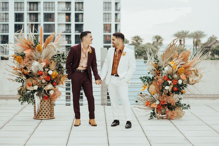 two grooms standing on rooftop wedding venue holding hands wearing retro 70s suits next to orange wedding decor and flower arrangements