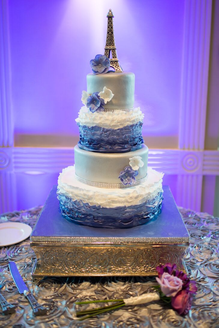 Edible Creations Cakes not only fit the couple's Parisian theme, but also complemented the day with a few whimsical details. Each of the confection's four tiers alternated between classic silver fondant and a fun, ruffled ombre detailing in purple. The cake topper also added a personal touch with an Eiffel Tower that complemented the couple's trip to Paris in 2010.