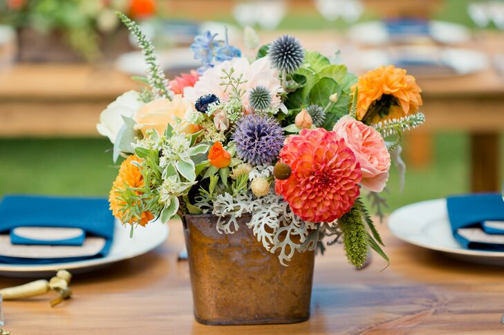 At the reception, wood dining tables were decorated with colorful, lush centerpieces of dahlias, roses, alliums and many other flowers accented with greenery.