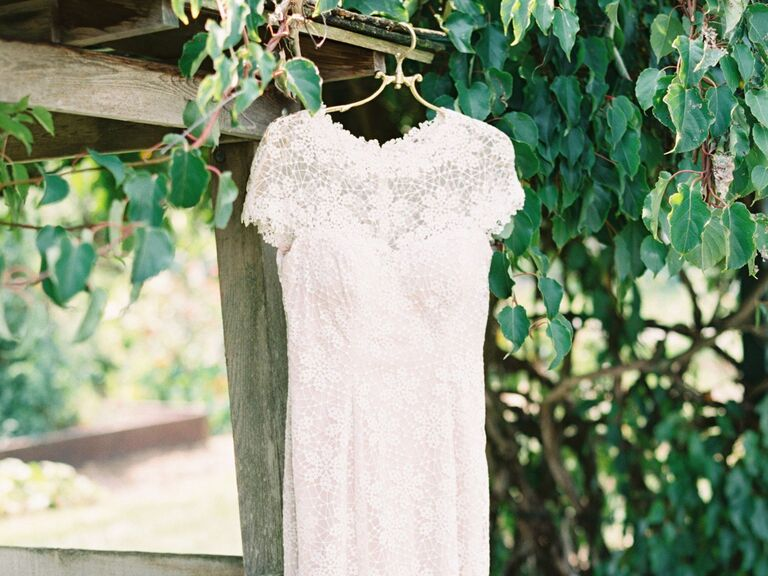 Simple lace wedding dress hanging outside