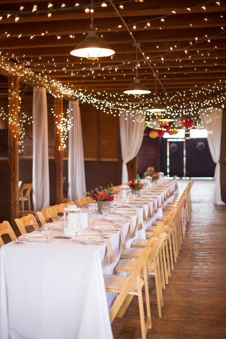 Strands of bulbs lit the barn space, providing a dreamy romantic mood. A long farm style table ran the length of the refurbished barn, with smaller round tables in what used to be horse stables on either side of the space.