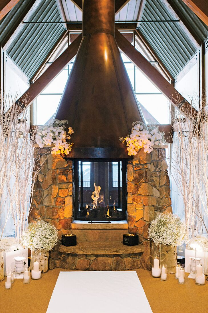 Josie and Kow married in front of a fireplace flanked by white branches, candles and arrangements of orchids and baby's breath.