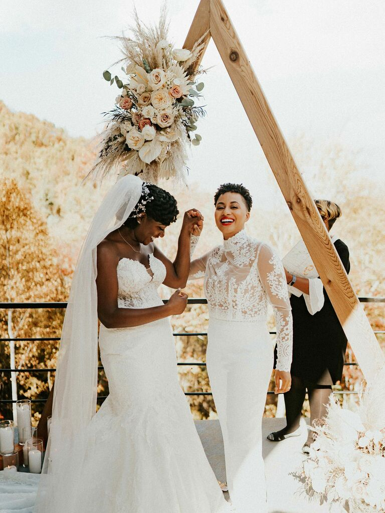 Brides holding hands in front of angular floral ceremony arch at outdoor summer wedding